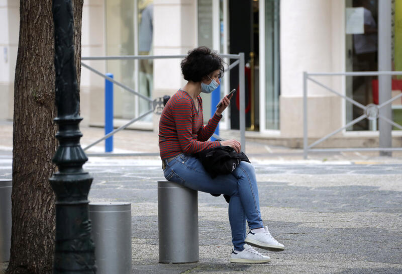 A woman, wearing a protective face mask, looks at her mobile phone in Nice following the outbreak of the coronavirus disease (COVID-19) in France, May 27, 2020. REUTERS/Eric Gaillard