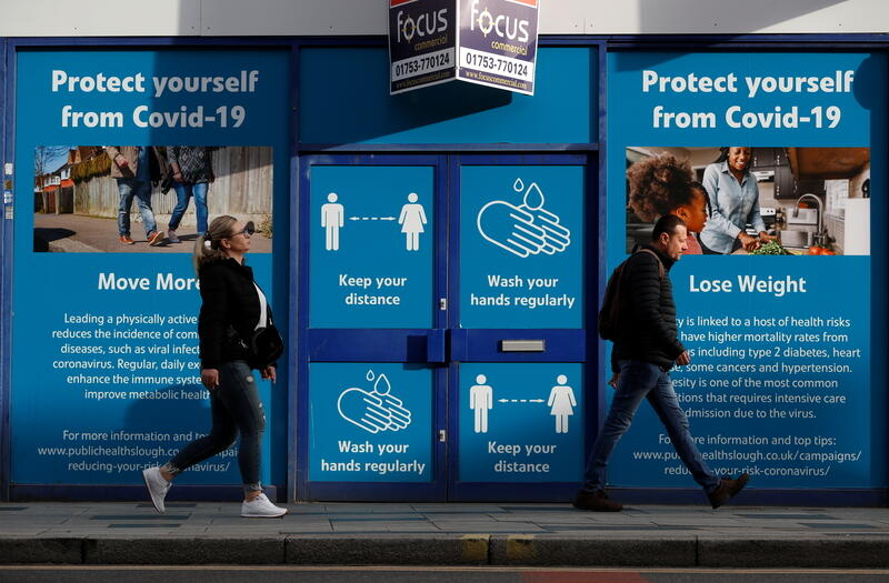 People walk past a signage about COVID-19 measures as the spread of the coronavirus disease (COVID-19) continues in Slough, Britain October 23, 2020. REUTERS/Paul Childs