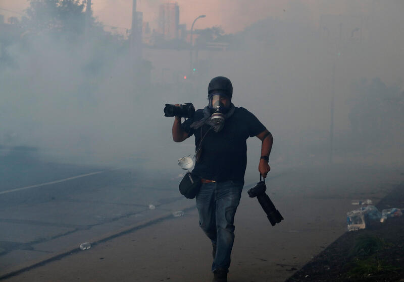 Photographer wearing facial protection REUTERS/Carlos Barria