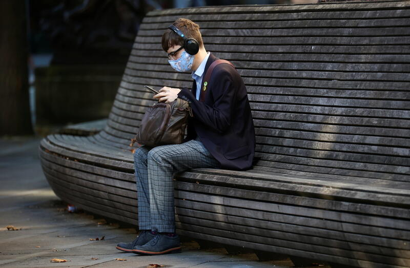 A person wearing a protective mask looks at a mobile phone in Manchester.