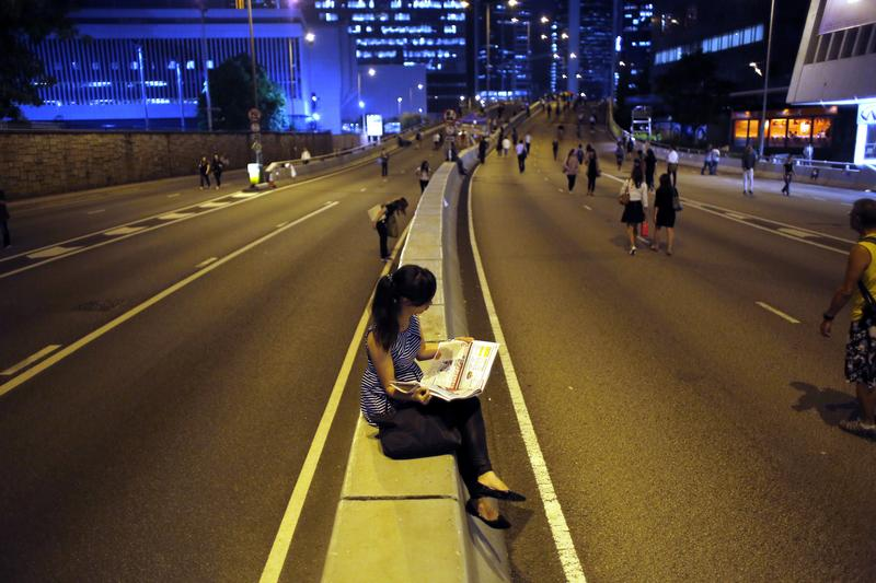 A pro-democracy protester reads a newspaper, Hong Kong. REUTERS/Carlos Barria