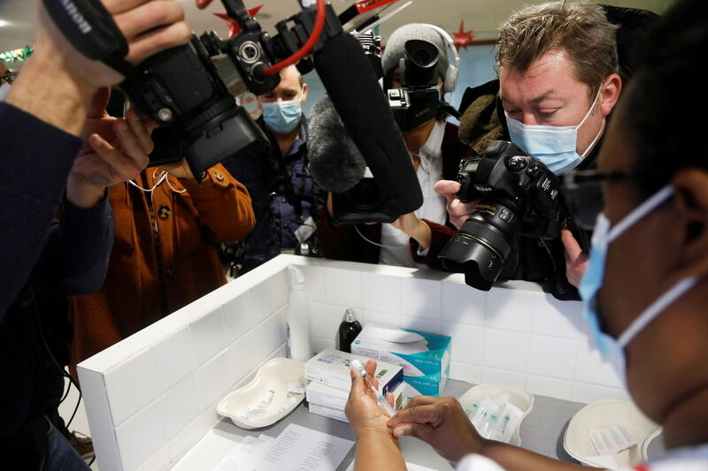 A nurse prepares a dose of the Pfizer-BioNTech COVID-19 vaccine, surrounded by media staff, Bobigny, France, December 30, 2020. REUTERS/Charles Platiau