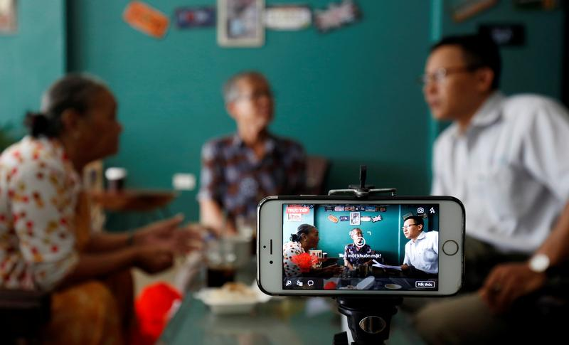Rights activist Le Van Dung (R) live streams on Facebook in a coffee shop in Hanoi, Vietnam May 15, 2018. Picture taken May 15, 2018. REUTERS/Kham