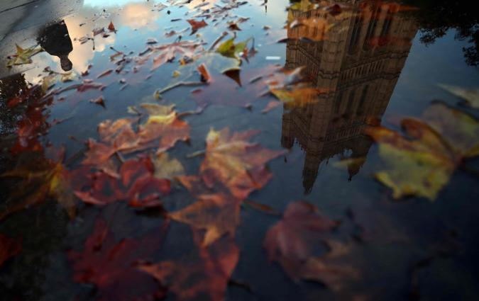 A man walking past the Houses of Parliament is reflected in a puddle. REUTERS / Hannah McKay