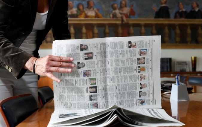 Journalist Daniela Taiocchi leafs through an edition of the newspaper L'Eco di Bergamo in which ten pages of obituaries have been published due to the high number of deaths from the coronavirus disease (COVID-19), in Bergamo, Italy May 12, 2020. Picture taken May 12, 2020. REUTERS/Flavio Lo Scalzo